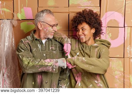 Cheerful Multiethnical Woman And Man Make Fits Bump Work As Team Discuss Home Decoraton Paint Interi