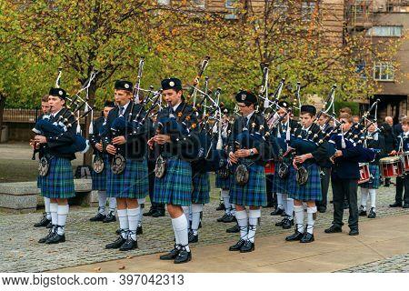 GLASGOW, UK - FEB 26, 2020: People perform bagpipes in team in street in Scotland, United Kingdom