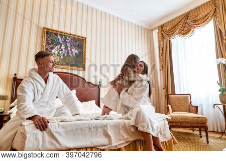 Caucasian Parents And Daughter In White Bathrobes Relaxing And Spending Morning Together. They Are S