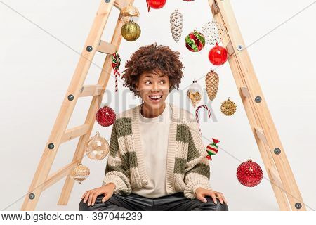 New Year Preparation And House Decoration. Cheerful Thoughtful Young Woman With Afro Hair Looks With