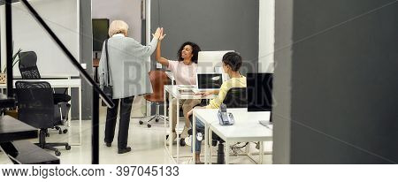 Full Length Shot Of Cheerful Aged Woman, Senior Intern Giving High Five, Saying Goodbye To Her Young