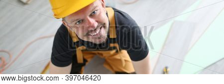 Smiling Carpenter In Helmet Sawing Laminate Flooring. Simple And Popular Layout Option. Protective V