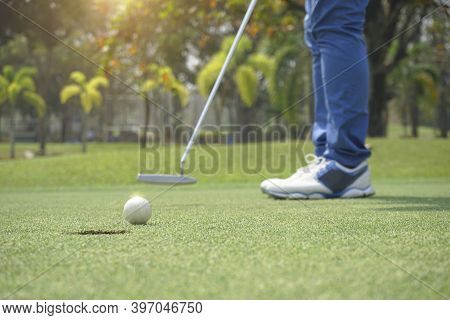 Golfer Playing Golf In The Evening Golf Course, On Sun Set Evening Time. Man Playing Golf On A Golf
