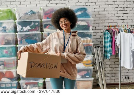 African American Girl Holding Donation Box And Smiling At Camera. Young Volunteer Working At Charity