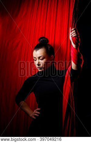 Portrait Of A Sports Girl On A Background Of Red Cloths For Aerial Gymnastics. Studio Shooting On A