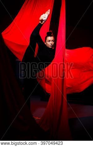 A Beautiful Sportive Girl Acrobat Performs Gymnastic And Circus Exercises On Red Silk. Aerial Gymnas
