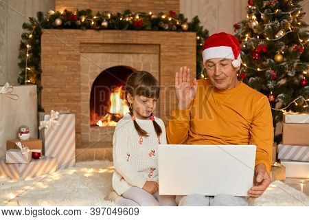 Grandfather And Granddaughter Having Video On Notebook, Waving Hands To Camera, Congratulating Someb