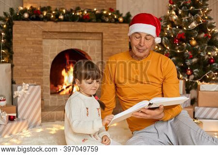 Elderly Man Reading Book With His Granddaughter In Living Room Decorated For Christmas, Family Sitti