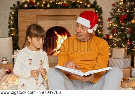 Mature Man Sitting On Floor And Holding Book In Hands, Looking At Her Granddaughter And Reading To C