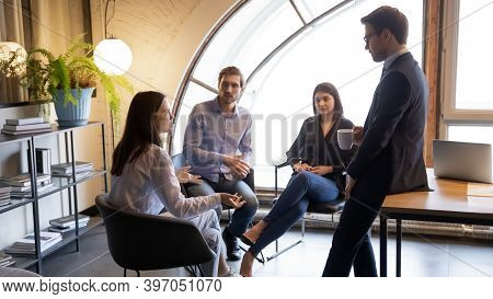 Young Multiracial Colleagues Friends Chatting On Informal Meeting In Office