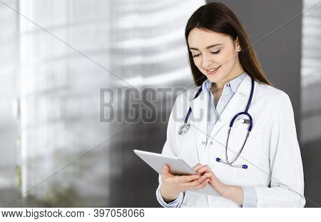 Cheerful Intelligent Woman-doctor Is Holding A Tablet Computer In Her Hands, While She Is Standing I