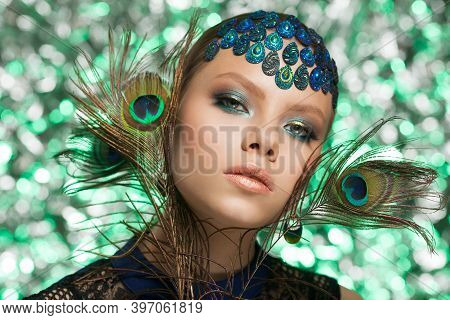 Beautiful Fashion Woman Face. Woman In Peacock Image With Peacock Feathers.