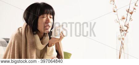 Young Woman Wrapped In A Plaid Looks Sick, Ill, Sneezing And Coughing Sitting On Sofa At Home Indoor