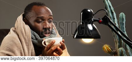 Young Man Wrapped In A Plaid Looks Sick, Ill, Sneezing And Coughing Sitting On Sofa At Home Indoors.