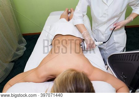 Rf-lifting Back In The Spa Salon For A Young Woman. Procedure Of Anti-cellulite Massage By The Elect