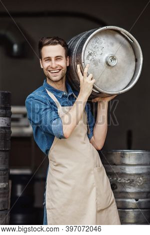 Products For Beer Fermentation And Employee On Modern Brewery. Portrait Of Smiling Strong Young Work