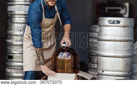 Work On Brewery And Warehouse With Metal Barrels. Strong Millennial Employee With Tattoo In Apron Pu