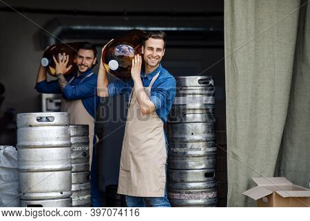 Working Day In Warehouse And Brewery Employees. Handsome Smiling Strong Millennial Men In Aprons Car
