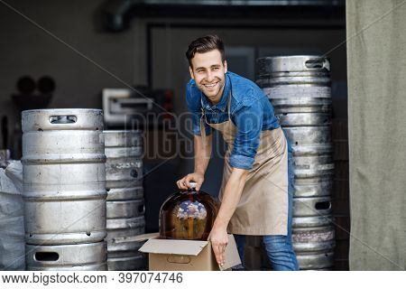 Small Business And Startup Brewery. Smiling Handsome Strong Millennial Worker Guy In Apron Pulls Out
