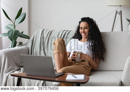 Relaxed Pretty Young Woman Watching Movie On Laptop, Drinking Coffee, Sitting On Sofa At Home, Copy