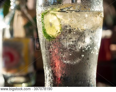 Cold Glass Of Soda Water With Ice-cubes And A Slice Of Lime. Condensed Water On The Outside Of The G