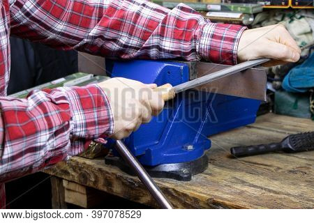 A Handyman With File For Metal. A Locksmith Vise. Blue Vise On A Wooden Table. Bench Tools. Vice. Me