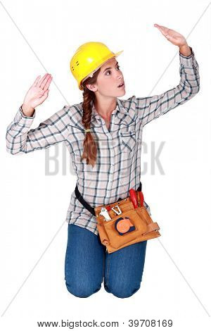 Tradeswoman patting invisible walls