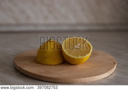 The Lemon Is Cut In Half On A Cutting Board. Two Lemon Halves Turned Upside Down With A Cut, The Oth