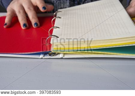Girl Hands And Binder Notebook With Color Separators And Chesquered Sheets. 4 Ring Binder. Copy Spac