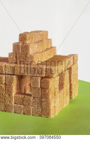 Sugar Addition. House Formed With Brown Cane Sugar Cubes On Rough Green Paper. Sweet Home. Concept.