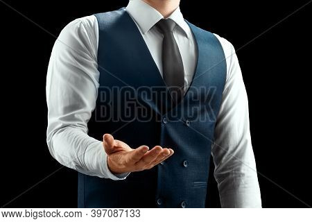 A Businessman In A White Shirt, Vest And Tie Holds Out His Hand To Us, Palm Up. Isolated On Black Ba