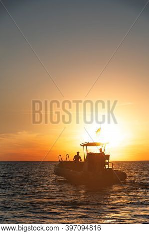 Silhouette Of A Catamaran Boat With A Man On Board At Sunset On The High Seas