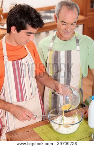 a teenage boy and a senior man making a cake