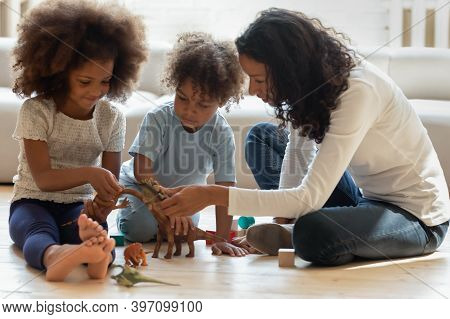 Pleasant Black Female Tutor Explaining Children Interesting Facts About Dinosaurs