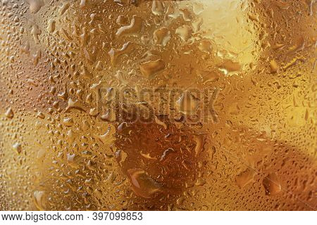 Texture Background Of A Glass Of Golden Whiskey Or Scotch Close - Up-drops And Misted Glass, Blurred