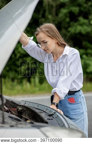 Young Woman Opening Bonnet Of Broken Down Car Having Trouble With Her Vehicle. Worried Woman Talking