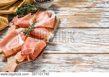 Spanish Jamon Serrano On A Cutting Board, Cured Ham. White Wooden Background. Top View. Copy Space