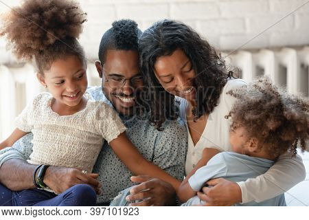 Joyful African American Parents Relax On Couch Tickling Children