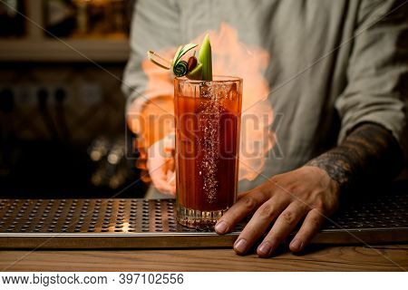Man Sets Fire To Glass Of Tomato Juice Cocktail Garnished With Slices Of Vegetables.