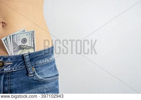 A Woman In Jeans With A Bare Stomach With Dollars Sticking Out Of Her Pants. The Concept Of Striptea