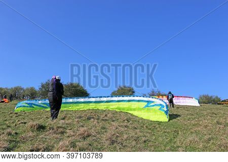 Paragliders Preparing To Launch Their Wings On A Hill