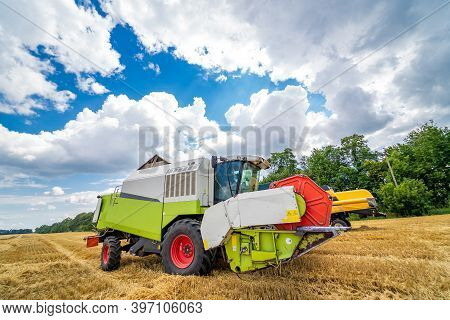 Combine Harvester In Action On Wheat Field. Process Of Gathering Ripe Crop From The Fields. Agricult