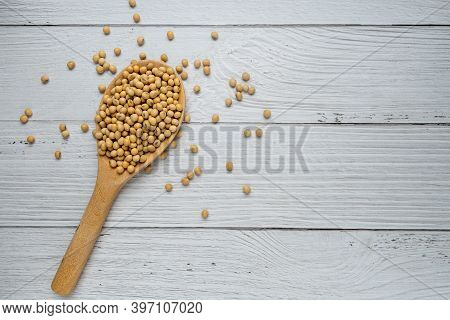 Soybeans Or Soya Beans In Wooden Spoon On White Wood Background. Top View. Vegan Food Concept