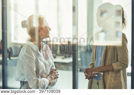 Two Diverse Female Coworkers Having Informal Conversation While Standing In The Modern Office