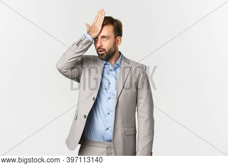 Portrait Of Annoyed Male Entrepreneur In Grey Suit, Slap His Forehead And Roll Eyes, Bothered By Som