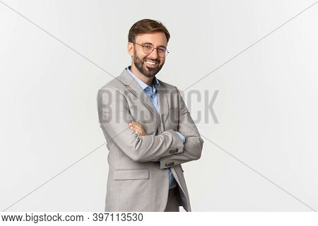 Portrait Of Confident Businessman With Beard, Wearing Grey Suit And Glasses, Cross Arms On Chest And