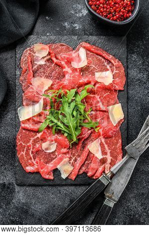 Beef Carpaccio On Black Plate With Parmesan Cheese And Arugula. Black Background. Top View