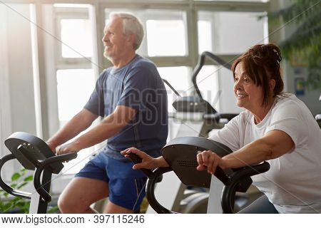 Elderly Woman Working Out In Modern Gym. Senior Caucasian Woman Using Using Bike For Cardio Workout