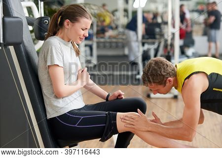 Unhappy Young Woman With Injured Knee At Gym. Young Fitness Trainer Helping An Injured Woman At Fitn