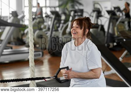 Woman Training Arms With Fitness Straps. Active Senior Woman Doing Special Exercise For Her Hands At